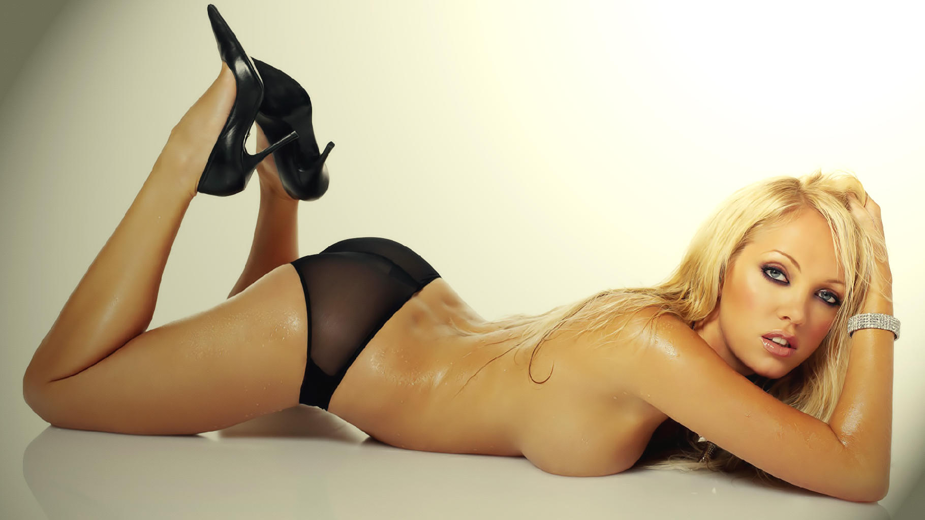 a sexy blonde escort on a bed