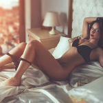 a sexy escort laying on a bed