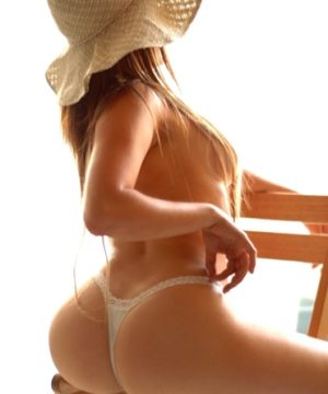 Brunette sitting on chair with hat on