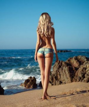 tall leggy blonde in denim shorts on beach